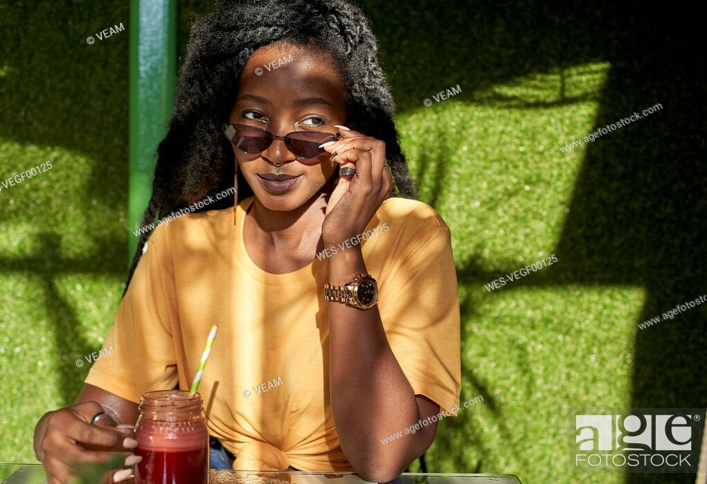 Stock Photo: Young woman with dreadlocks having a smoothie in a cafe.