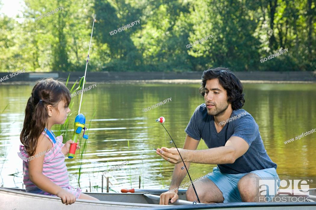 Stock Photo: Father and daughter on rowboat with fishing rods.
