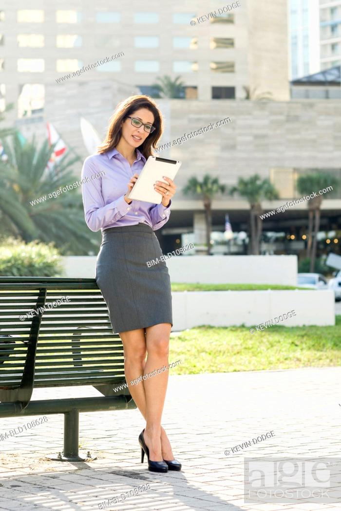 Stock Photo: Hispanic businesswoman leaning on bench using digital tablet.