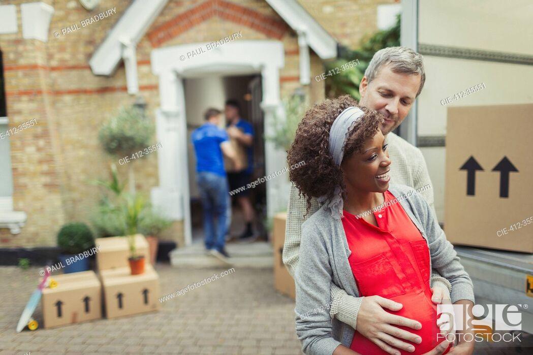 Photo de stock: Multi-ethnic pregnant couple moving into new house.