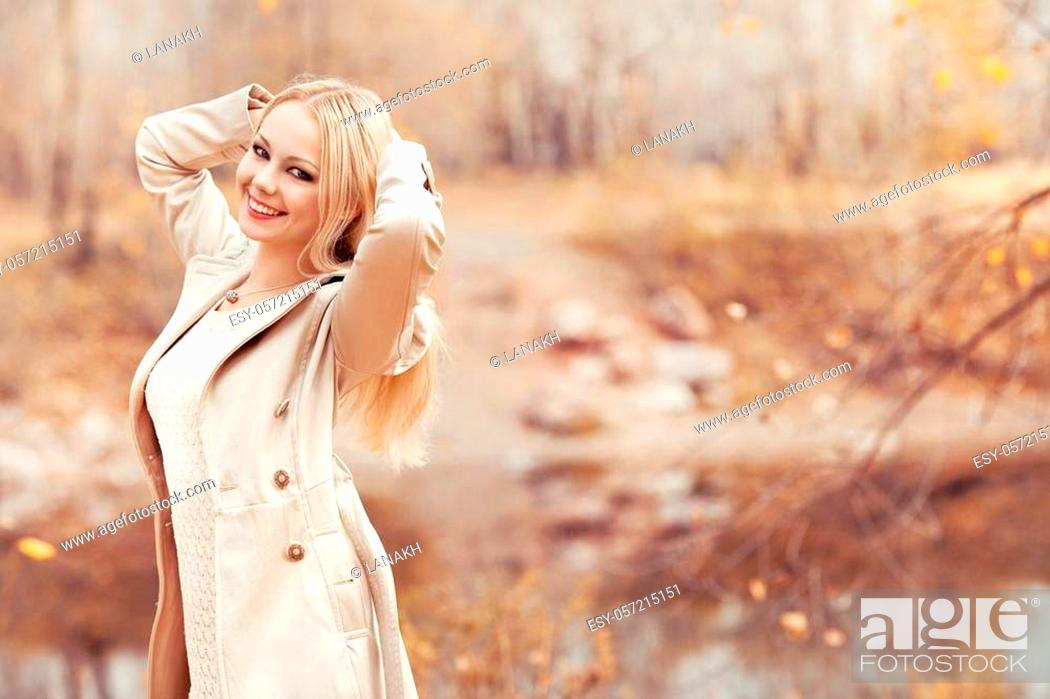 Stock Photo: happy stylish blond woman walking in the autumn park.