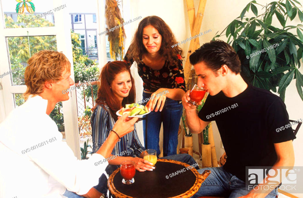 Stock Photo: Two young couples eating and drinking.
