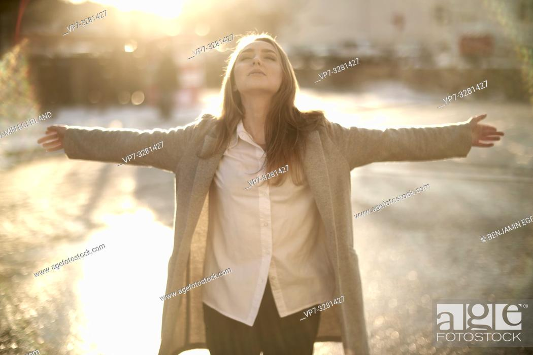 Stock Photo: young woman outdoors in sunlight at street in city, in Cottbus, Brandenburg, Germany.