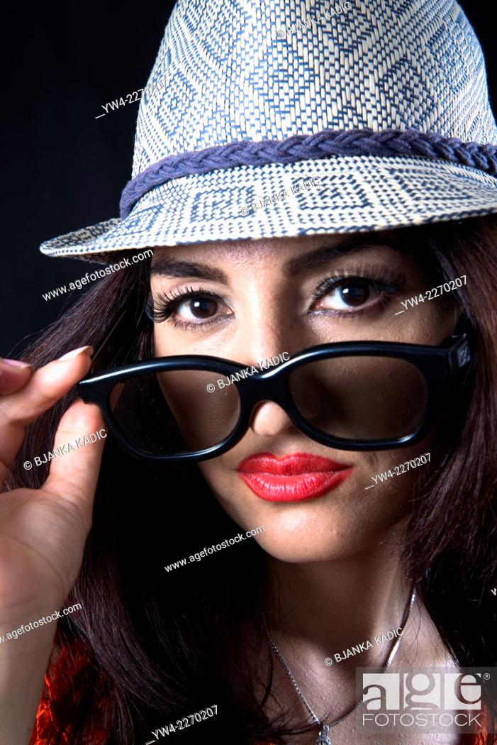 Stock Photo: Woman wearing trendy small hat and sunglasses.