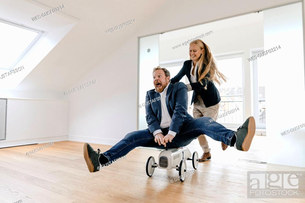 Stock Photo: Playful businesswoman pushing businessman on toy car in office.
