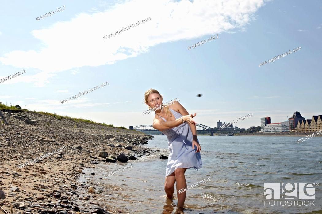 Stock Photo: Germany, Cologne, Young woman skipping stones in river.