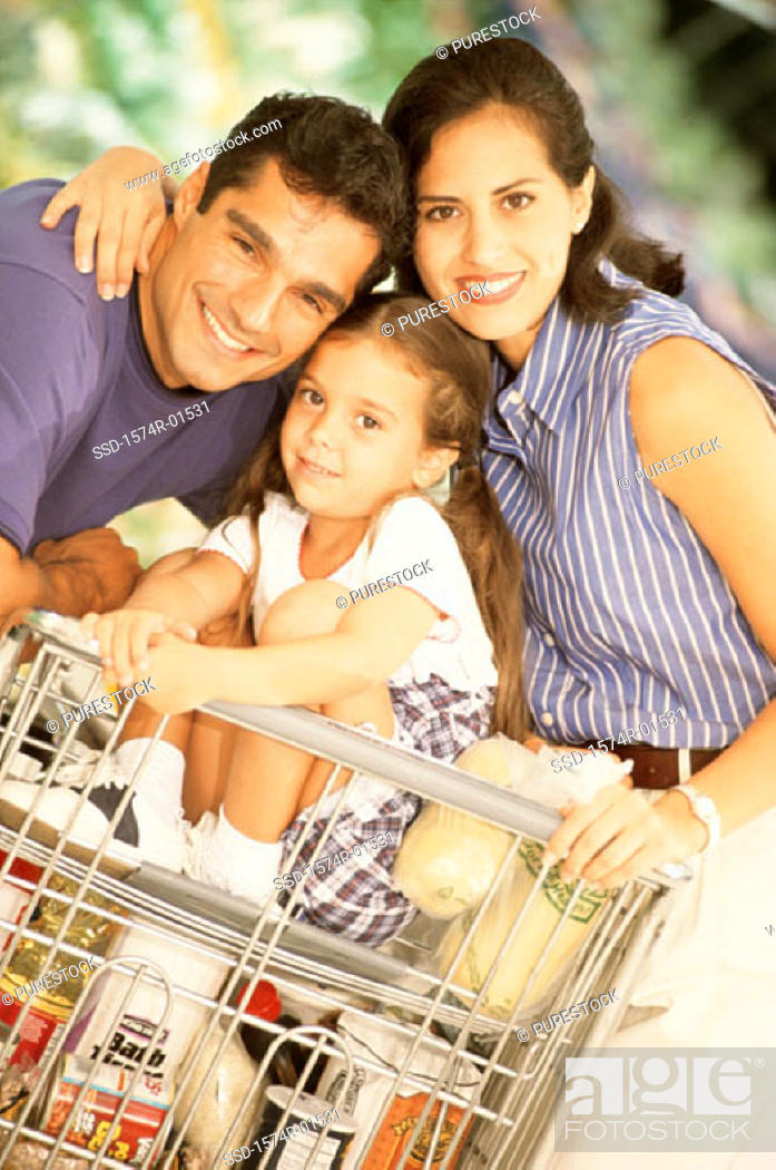 Stock Photo: Portrait of a couple with their daughter sitting in a shopping cart.