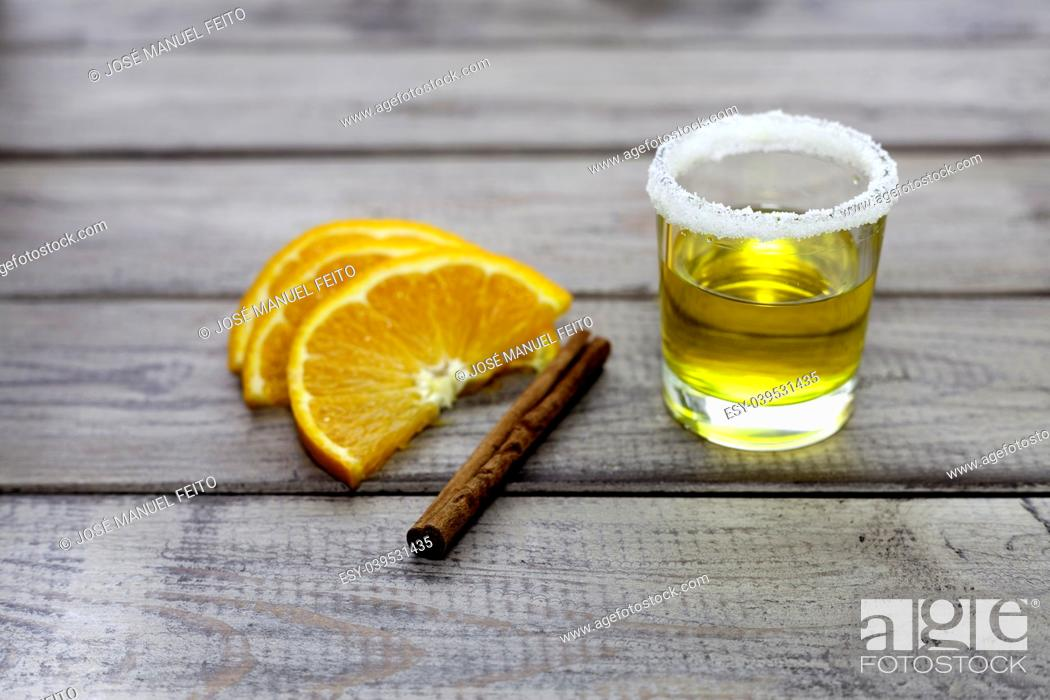 Stock Photo: tequila shot with orange slice and cinnamon on wood background.