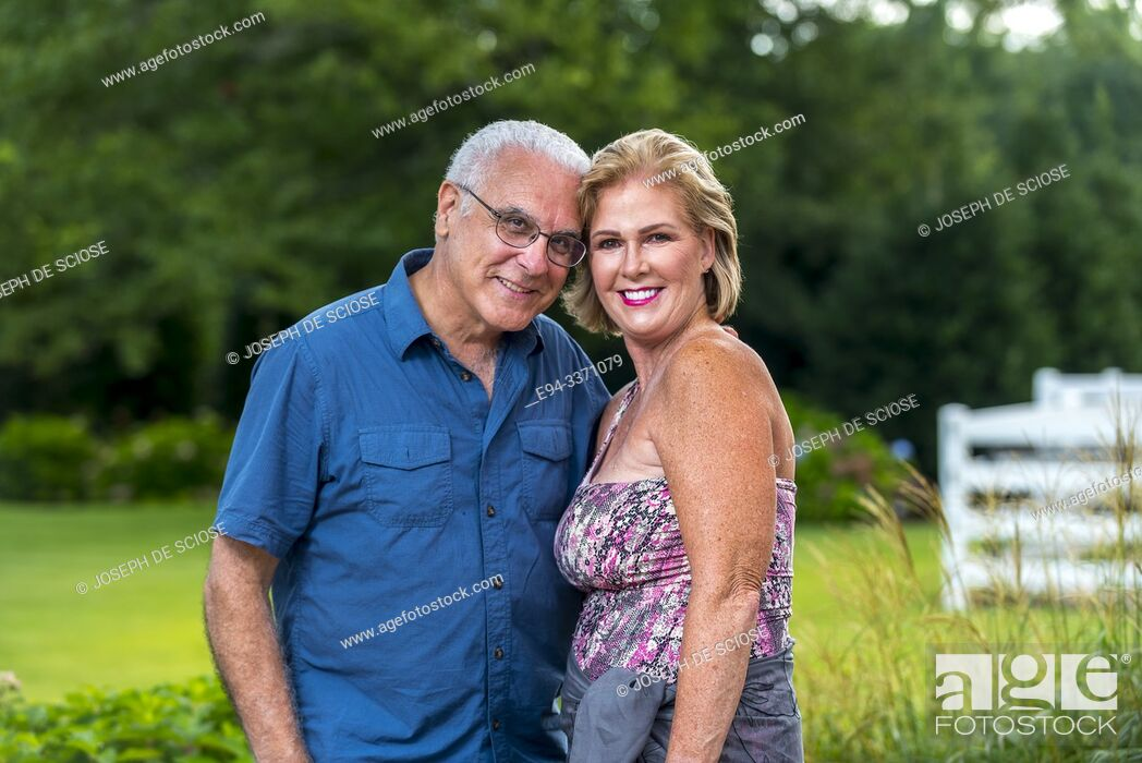 Stock Photo: A happy 60 Year old blond woman and a 66 year old man smiling at the camera, outdoors.