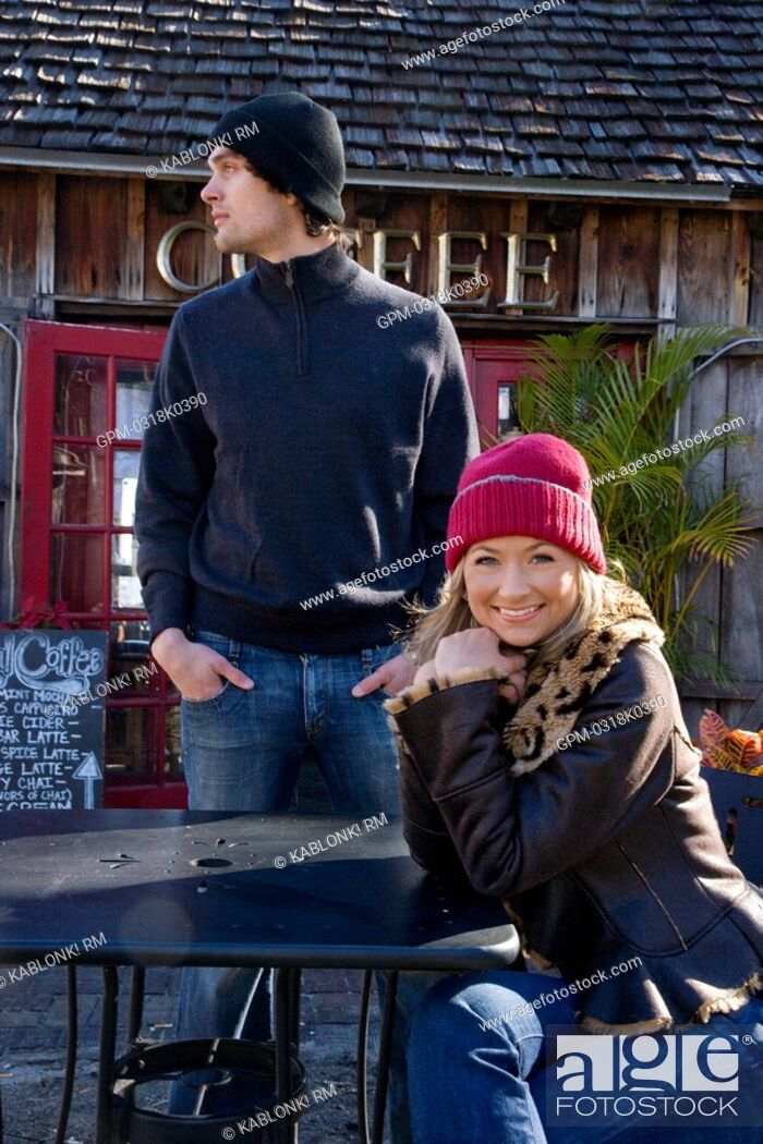 Imagen: Portrait of young couple in warm clothing sitting at outdoor coffee shop.