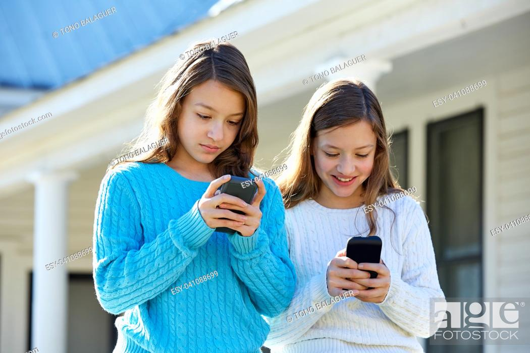 Imagen: Sister twins having fun with technology mobile smartphone.