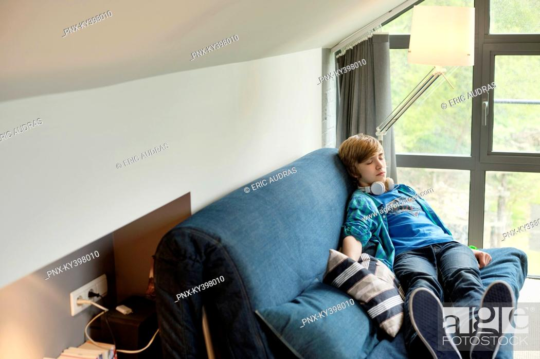 Stock Photo: Teenage boy sleeping on a couch at home.