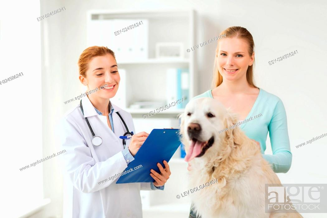 Stock Photo: medicine, pet, animals, health care and people concept - happy woman with golden retriever dog and veterinarian doctor writing to clipboard at vet clinic.