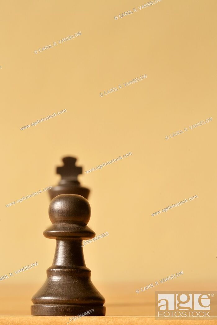Stock Photo: Pawn confronting a king. Both pawn and king are dark wood. Shot with shallow depth of field.