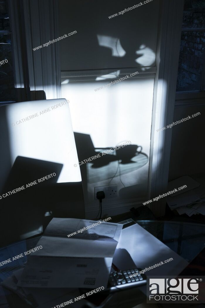 Imagen: Shadows of work and office paraphernalia with a glass top table, paper work, coffee cup and laptop plugged into a power socket, Bristol, England.