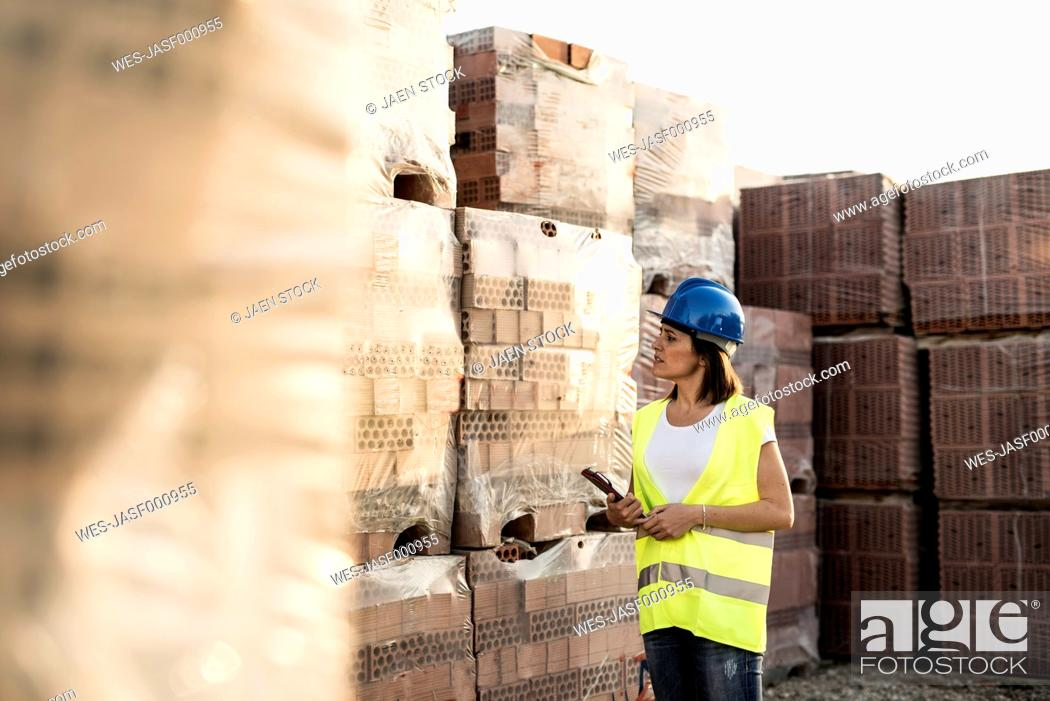 Stock Photo: Female construction worker checking building materials.