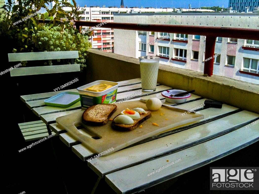 Imagen: Berlin, Germany. Cozy breakfast at a plattenbau apartment's balcony during a sunny, summer morning.