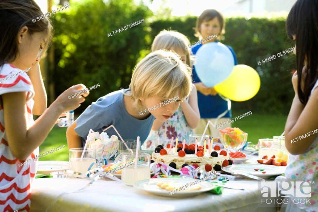 Stock Photo: Boy blowing candles on birthday cake at outdoor birthday party.
