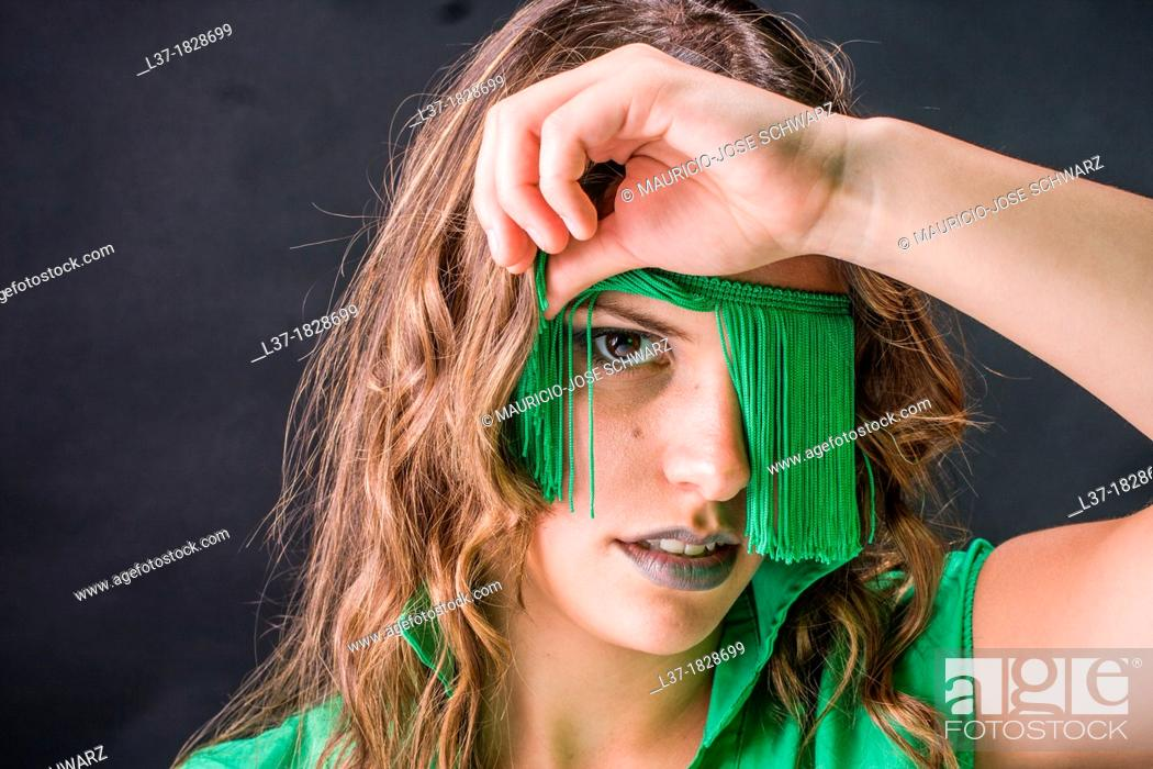 Stock Photo: Young woman looking out from a blindfold of green fringes.