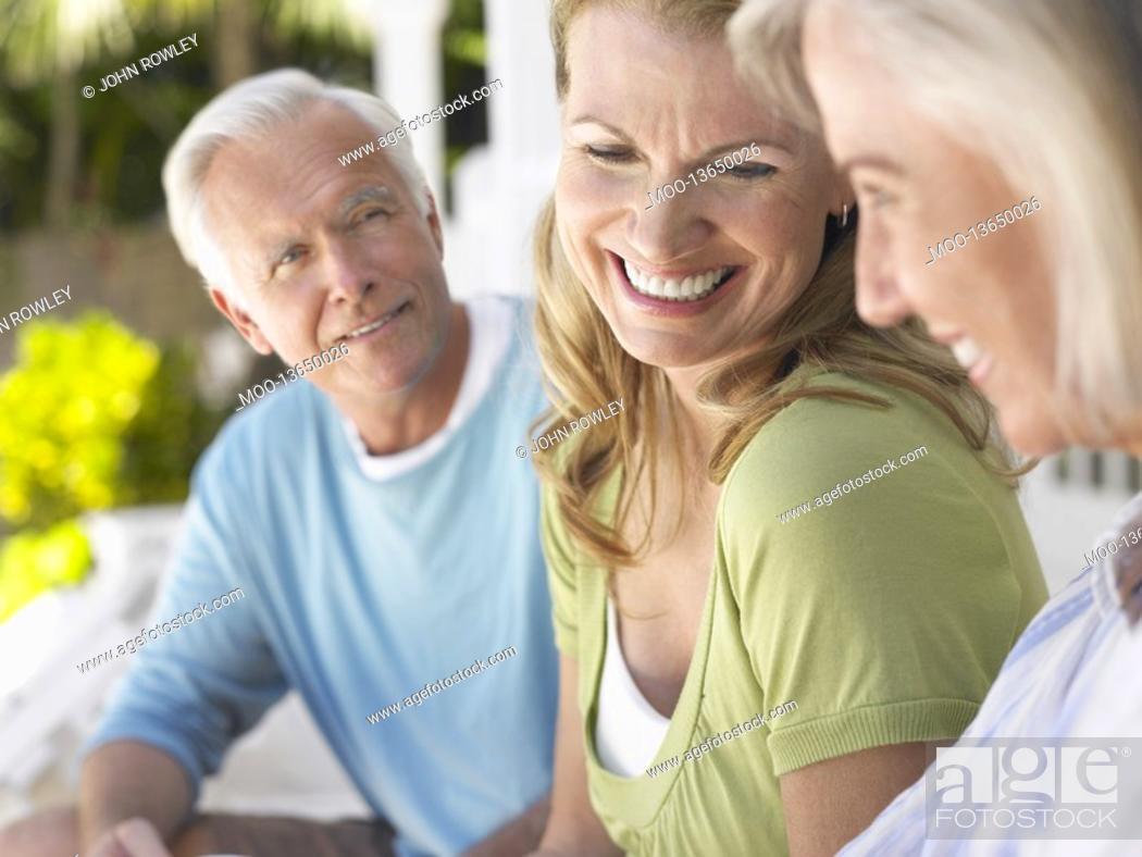 Stock Photo: Three people sitting on verandah.