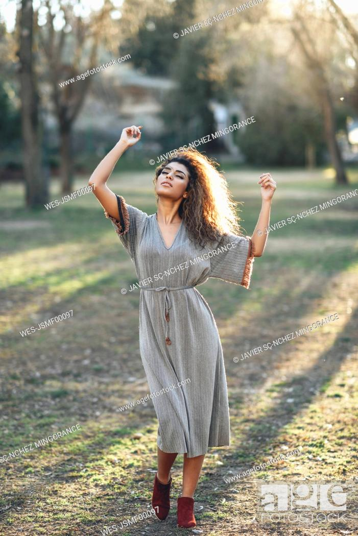 Imagen: Fashionable young woman dancing in a park in the evening.