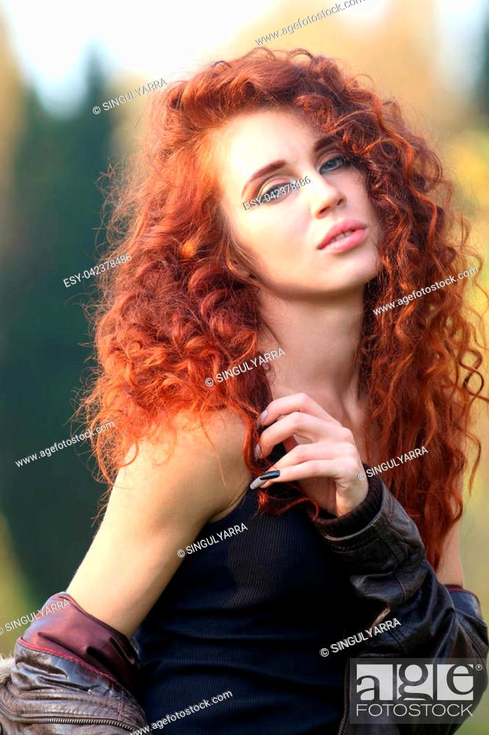 Stock Photo: Beautiful woman with red hair in leather jacket poses in forest, shallow dof.