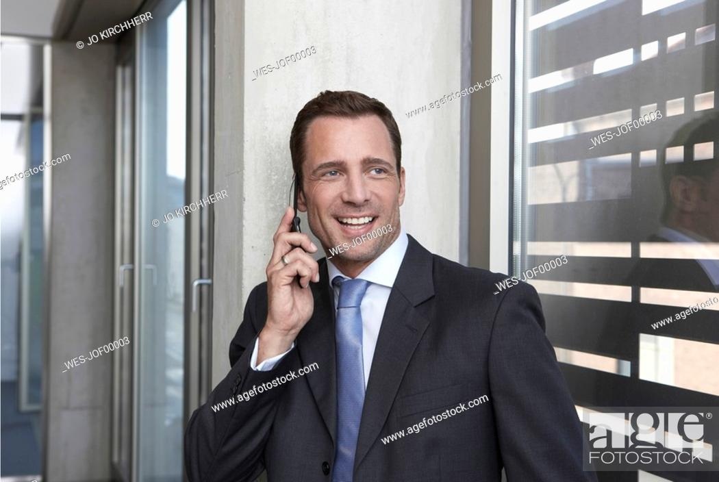 Stock Photo: Germany, Cologne, Businessman leaning against wall using mobile phone, smiling, portrait.