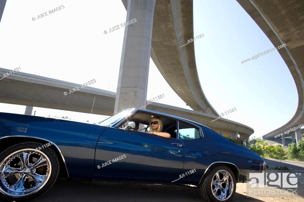 Stock Photo: Young couple in car beneath overpass, low angle view lens flare.