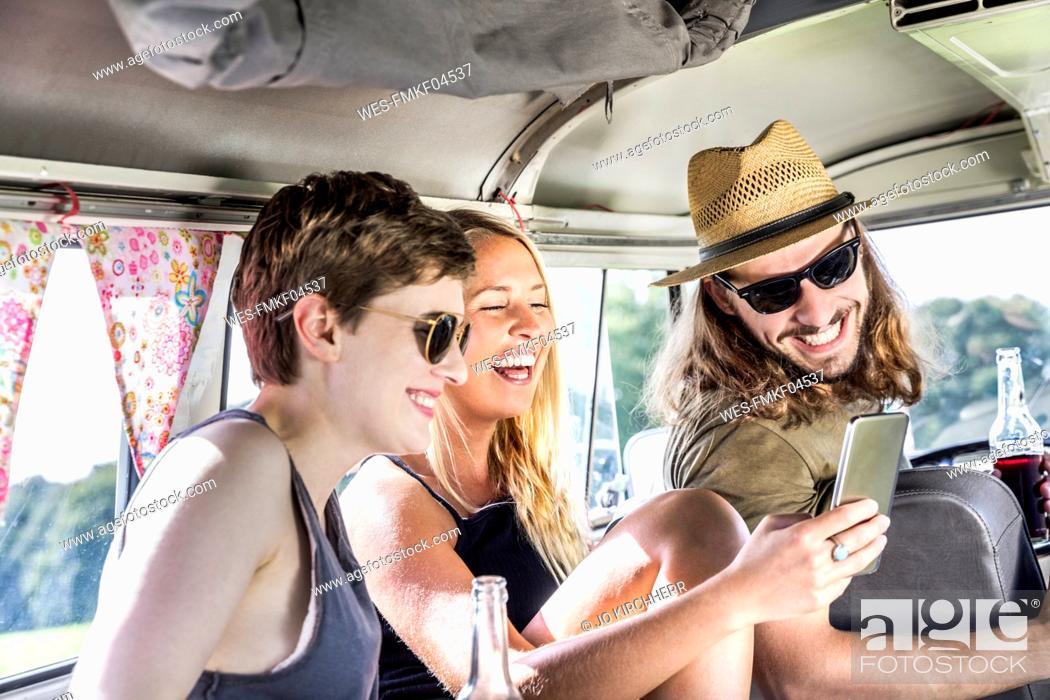 Stock Photo: Happy friends inside van looking at smartphone.