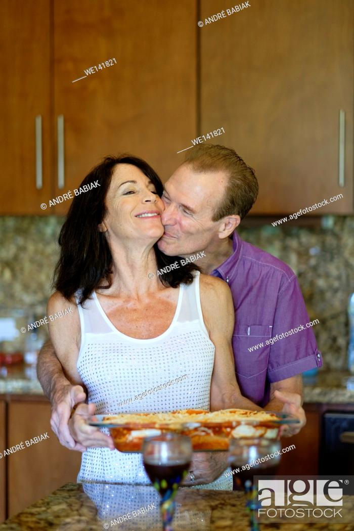 Stock Photo: Senior man and woman huggin and kissing in the kitchen while preparing dinner.