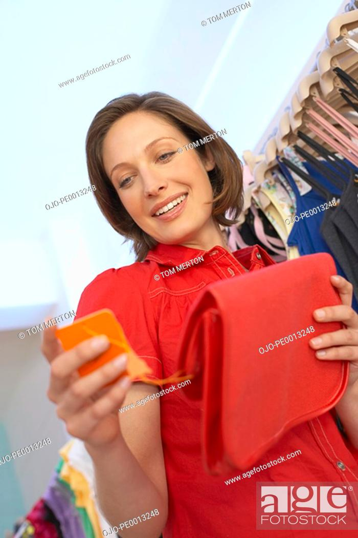 Stock Photo: Woman looking at sales tag on purse.
