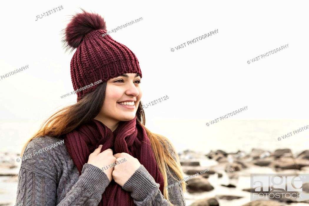 Stock Photo: Girl standing on a beach in autumn wearing a knit hat and scarf, Woodbine Beach; Toronto, Ontario, Canada.