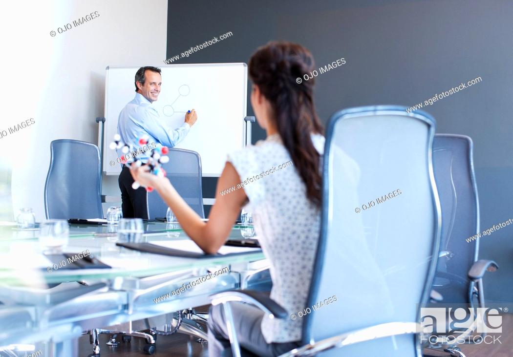 Photo de stock: Business people working with molecule model in conference room.