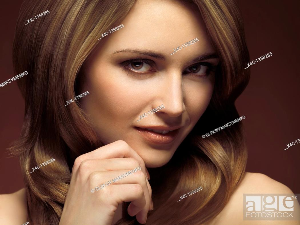 Stock Photo: Portrait of a beautiful young woman with a trendy glamorous hairstyle with highlights.