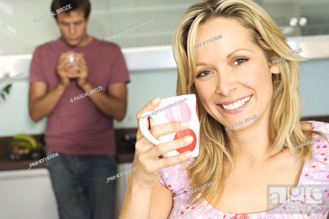 Stock Photo: Couple holding mugs in kitchen.