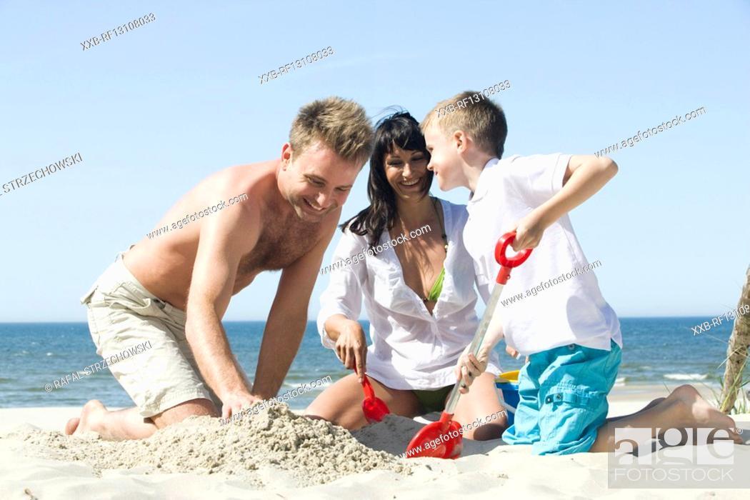 Stock Photo: family building sand castle.