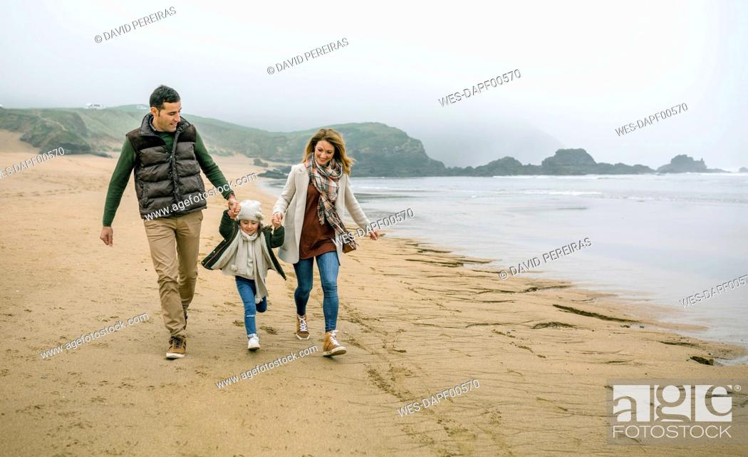 Stock Photo: Happy family with daughter walking on the beach in winter.