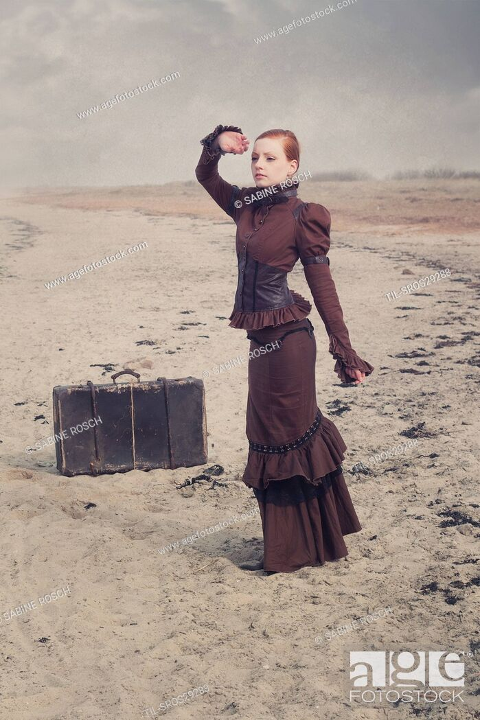 Stock Photo: Young woman in a victorian dress standing next to an old suitcase alone outdoors beside the sea.
