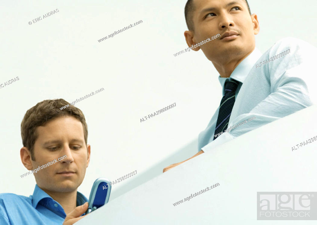 Stock Photo: Two businessmen, one looking at cell phone.
