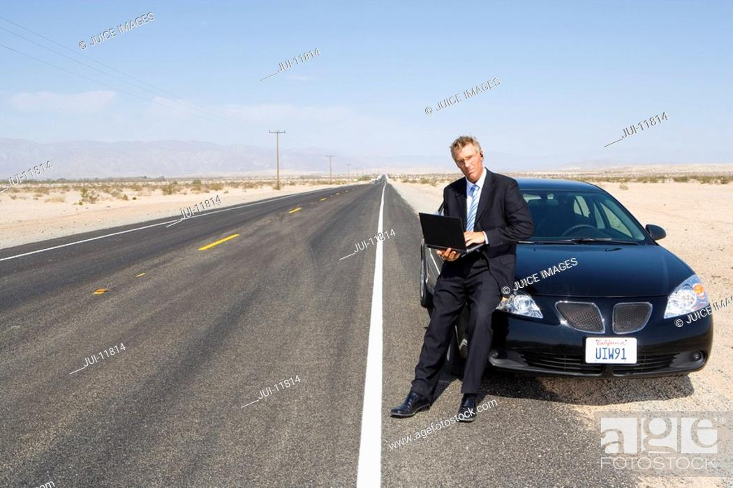 Stock Photo: Businessman by car on open road in desert, using laptop computer, portrait.