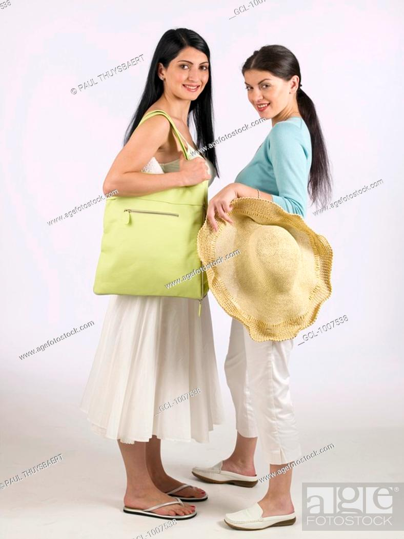 Stock Photo: Two women holding sunhat and green handbag.