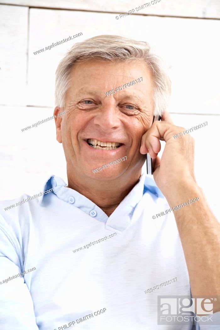 Stock Photo: Spain, Senior man talking on mobile, smiling, portrait.