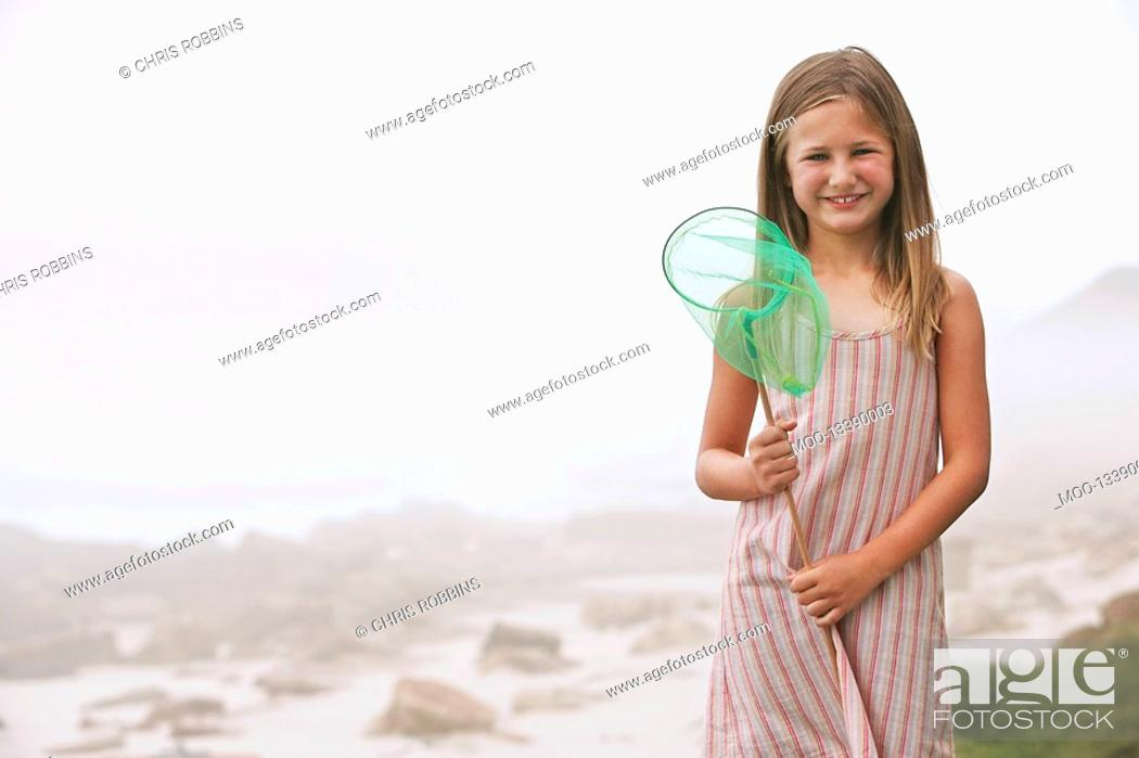 Stock Photo: Girl 7-9 holding fishing net standing on beach portrait.