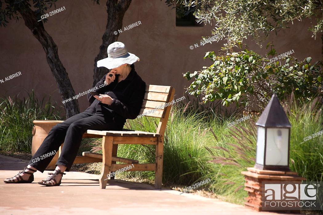 Stock Photo: Senior woman with sun hat, sitting on a public wooden bench, reading her tablet, in a garden, Marrakech, Morocco.