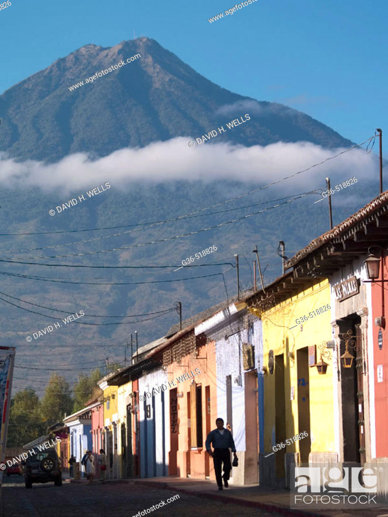 Stock Photo: A view of the nearby vocano and the colorfully painted Colonial style houses in Antigua, Guatemala.