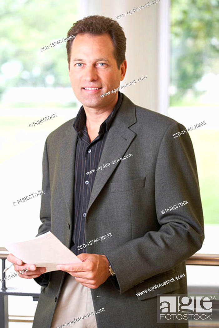 Stock Photo: Portrait of a professor holding a paper and smiling.