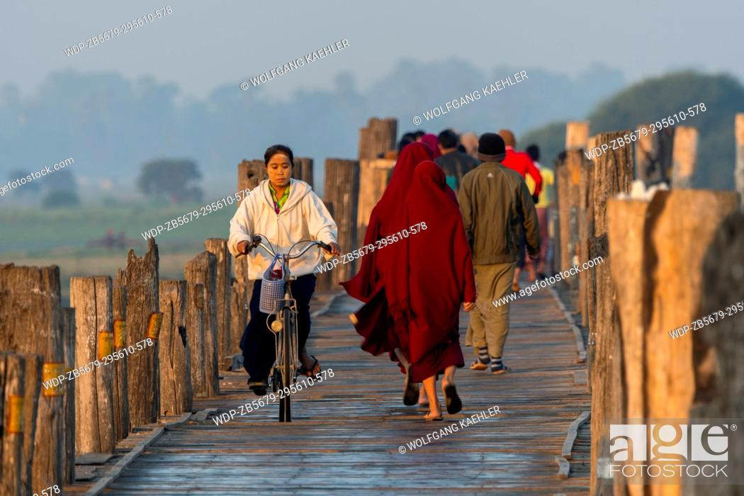Stock Photo: People on U Bein Bridge (built around 1850 and is believed to be the oldest and longest teakwood bridge in the world) spanning Taungthaman Lake near Amarapura.