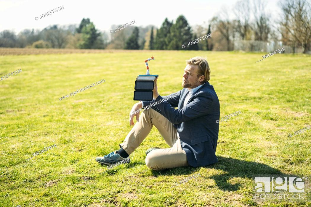 Stock Photo: Businessman analyzing robot arm while charging with portable solar panel at park on sunny day.