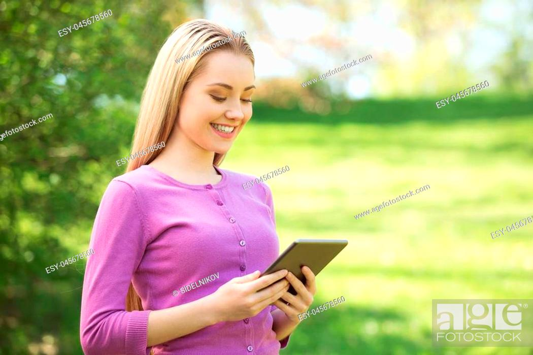 Stock Photo: Nice looking young woman outdoors. Woman using tablet computer. Beautiful green park as a background.