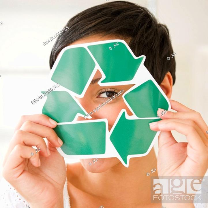Stock Photo: Mixed race woman holding recycling symbol in front of face.